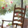Roses behind rocking chair.