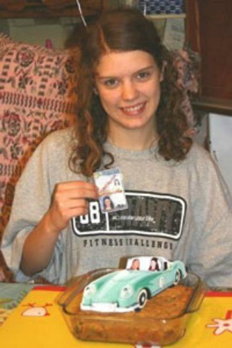 Girl holding license with cookie topped with car cutout.