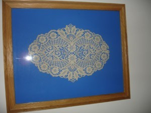 An antique doily in a frame.