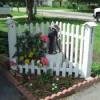 White corner fence in flower bed.