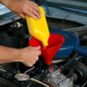 Adding oil to a car engine.