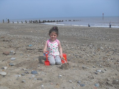 A girl playing at the beach in California.