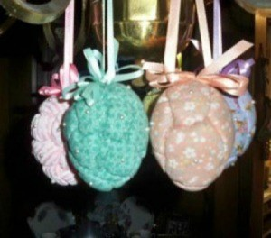 Easter eggs with a quilted appearance hanging from a chandelier.