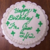 A white cake with green writing and shamrocks.