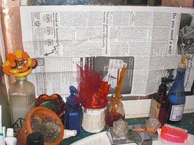Newspaper Shield When Steam Cleaning - Newspaper taped up behind small bottles.
