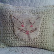Cat pot holder attached to crochet pillow.