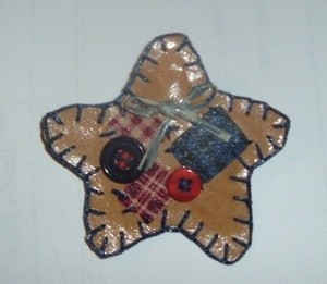 Paper star pin decorated with buttons and fabric.
