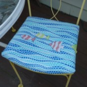 A chair seat covered with a cheerful blue seat cover with fish.