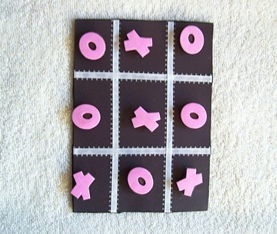 Black game board with pink Xs and Os.