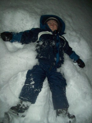 Boy making a snow angel.
