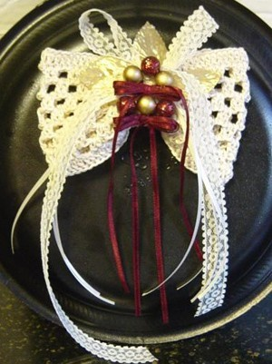 Crocheted hair bow with ribbon trim.