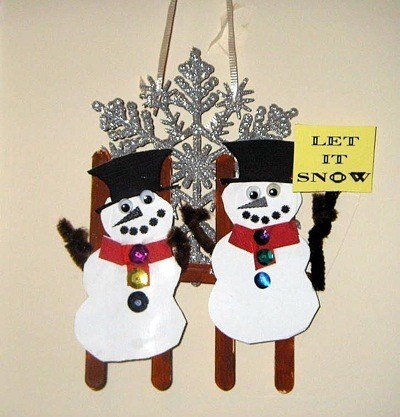 snowmen against fence with a large snowflake