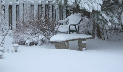 Snow covered garden chair, bench, and ground.