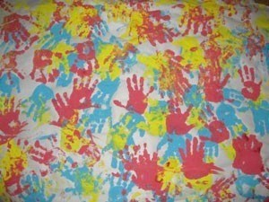blue, yellow, and red handprints on paper