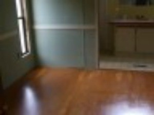 A stained wood flooring in an empty bedroom.