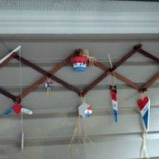 An expandable coat rack with red, white and blue ornaments hanging from it.