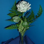 Rose made from dollar bill attached to stem and in vase.