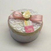 Round box decorated with buttons and pink ribbon.