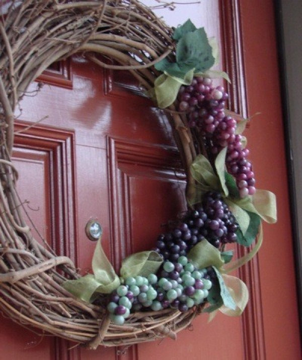 A grapevine wreath decorated with artificial grapes and leaves.