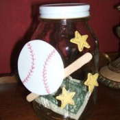 A piggy bank made from a recycled jar decorated with baseball motifs.