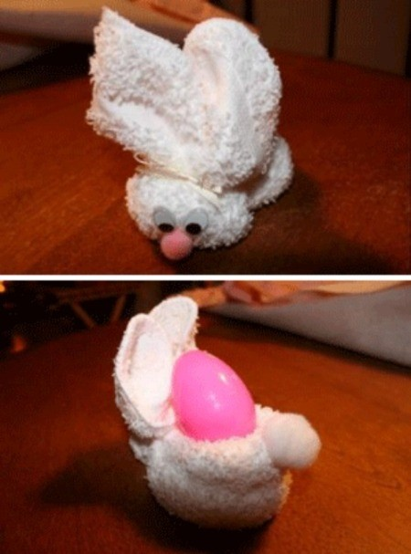 White towel folded into an Easter bunny with plastic egg in pouch.