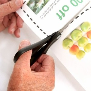 Scissors cutting out a coupon from a sheet of paper.