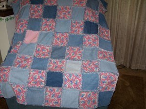 A denim and pink quilt made from recycled fabrics.