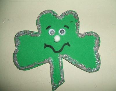 A green shamrock shaped pin made out of foam.