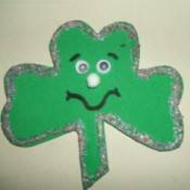 A green shamrock shaped pin made out of foam.