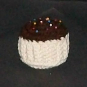 Crochet pin cushion in the shape of a cupcake.