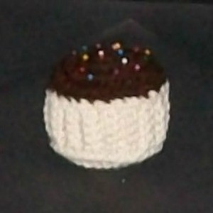 Crochet pin cushion in the shape of a cupcake.