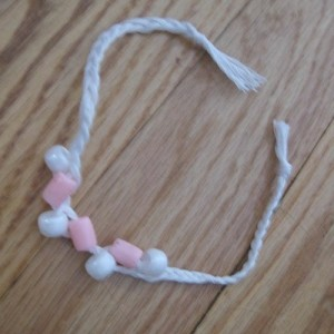 White bracelet with pink and white beads.