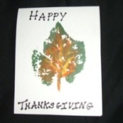 A homemade happy Thanksgiving card with a painted leaf design.