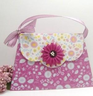 A handmade pink card that resembles a purse.