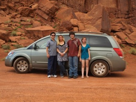 A family posing for a photo in front of a car.