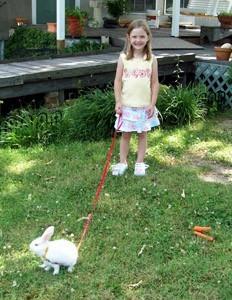 Girl walking a white rabbit.