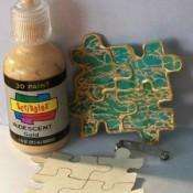 Metallic glue decorating puzzle pieces to make a decorative pin.