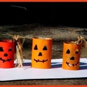 A collection recycled cans decorated to resemble jack-'o-lanterns.