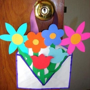 brightly colored paper flowers in decorated envelop basket