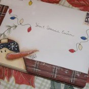 A Christmas card envelope with hand drawn snowman and string of lights.