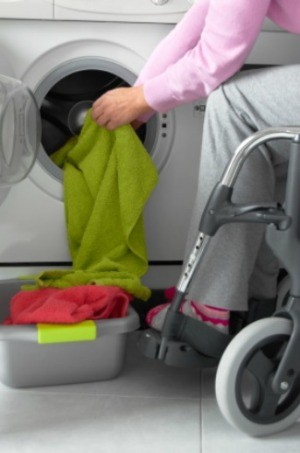 In a wheelchair doing laundry.