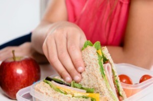 A girl eating packed lunch at school.