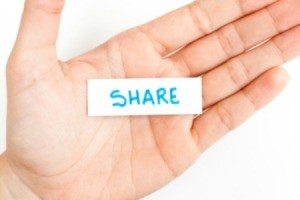 """A hand with a  note that says """"share""""."""