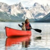 A woman paddling a canoe alone.