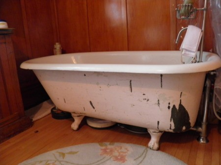 Clawfoot tub with peeling paint.