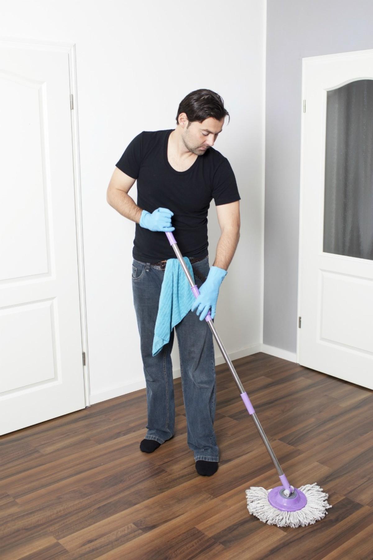Man Removing Wax From Laminate Flooring