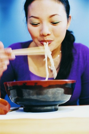 An Asian lady eating the frugal meal of ramen noodles.