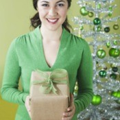 A woman holding a gift wrapped in recycled paper.