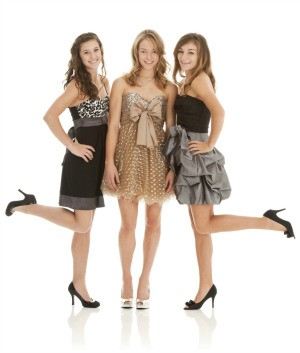 Three girls wearing prom dresses.