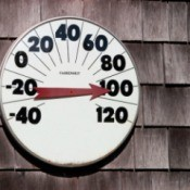 A thermometer on the side of a house reading 100 degrees fahrenheit.